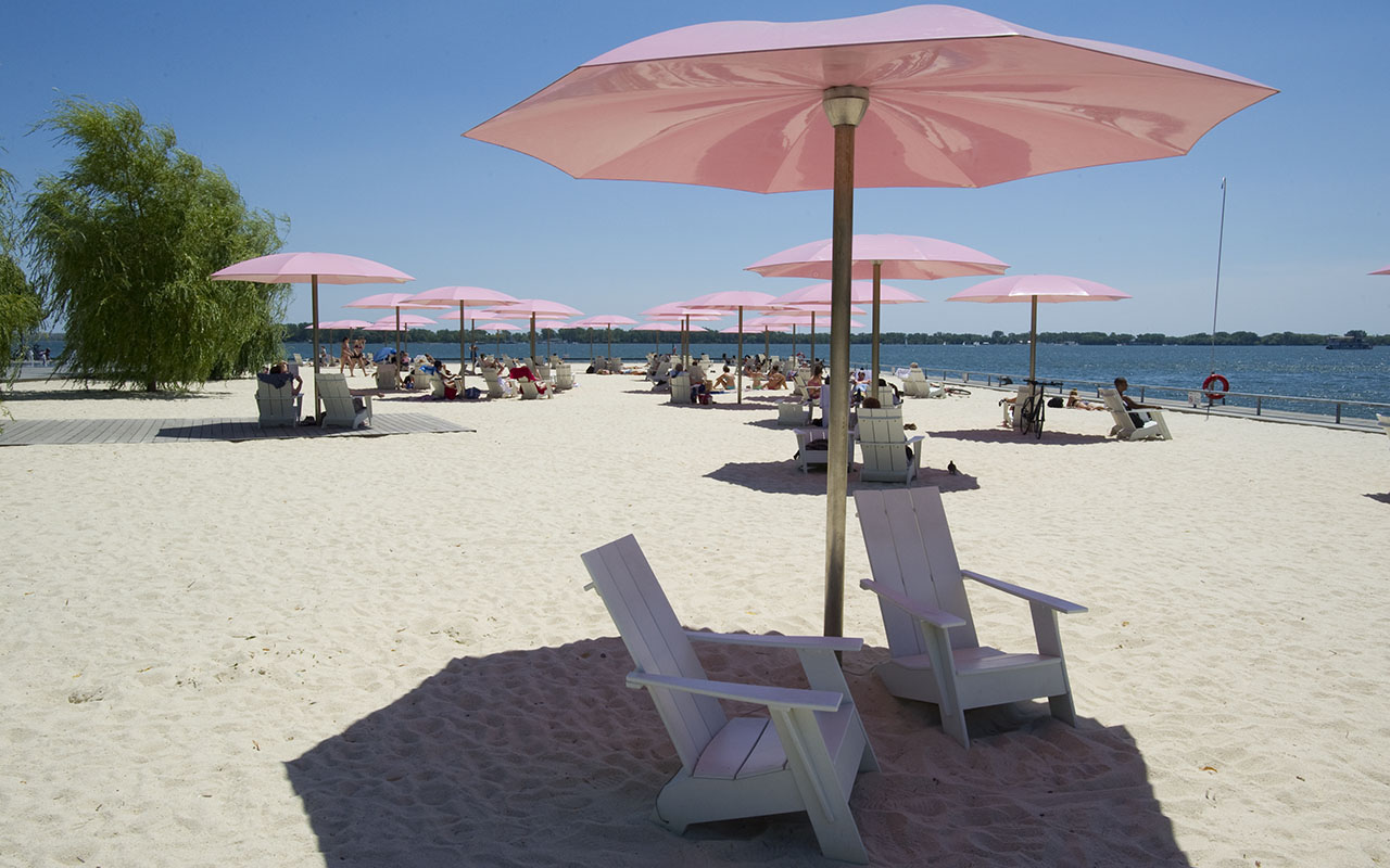 White loungers under pink umbrellas in the white sand of Sugar beach looking out into the harbour.  Photo of Sugar Beach.