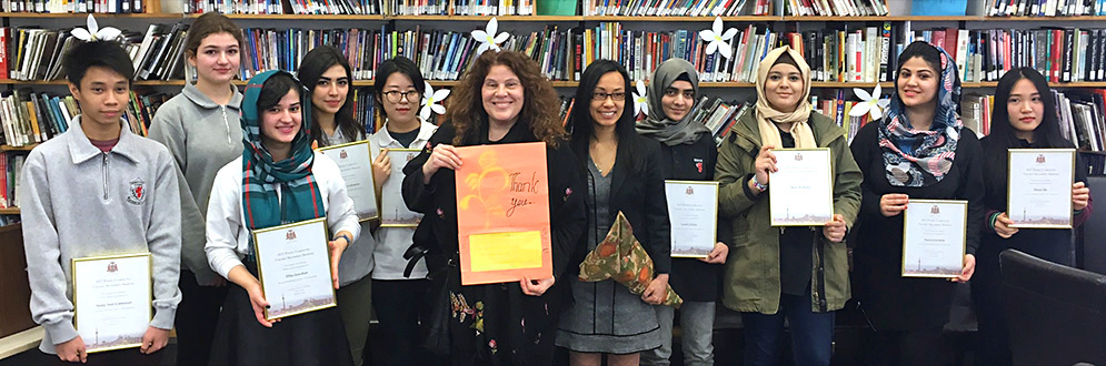 Toronto's Poet Laureate, Anne Michaels, stands with a group of teenagers in a library