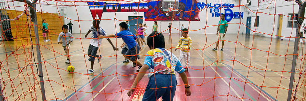 kids playing indoor soccer in a school gym