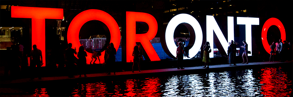 toronto sign lit up with red and white