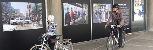 Two people on bicycles looking at a photo exhibition at City Hall regarding the intersection at Yonge and Dundas