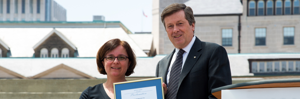 Mayor John Tory presents a framed proclamation to a woman