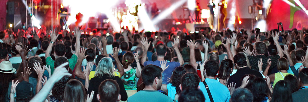 photo of a large crowd dancing in front of a concert stage during a performance