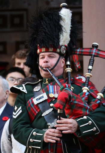 Scottish bagpiper playing The Lament to the Fallen at the Remembrance Day ceremony, Old City Hall Toronto
