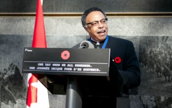 George Elliott Clarke delivering a speech next to a Canadian flag