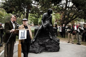 Dennis Lee standing with philanthropist Scott Griffin unveiling a bronze-statue of poet Al Purdy in Queen's Park