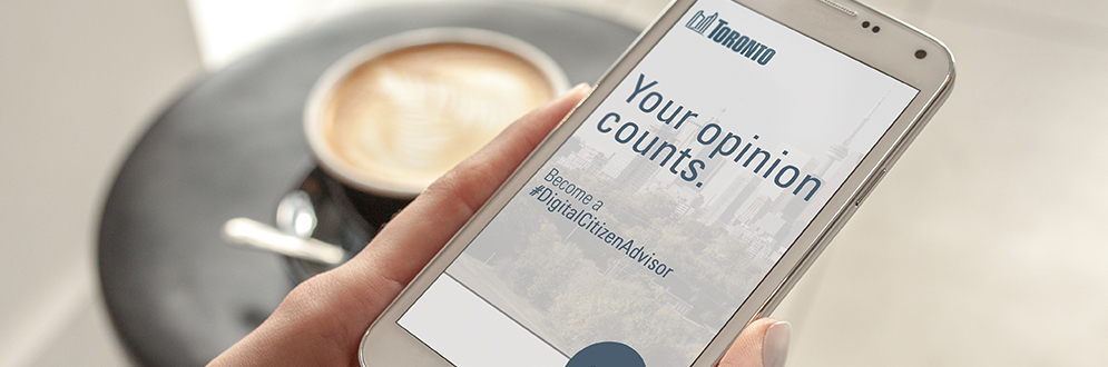 Person holding cellpohne that says, your opinion counts. become a digital citizen advisor