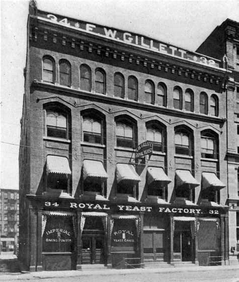Written across the top of the facade of this four-storey building is: F.W. GILLETT. On the front of the building is written: ROYAL YEAST FACTORY. Lettering on the front display windows says: IMPERIAL BAKING POWDER AND ROYAL YEAST CAKES.