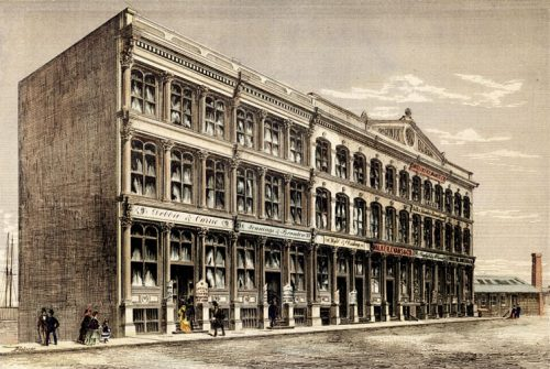 This hand-coloured newspaper print shows a three-storey block of buildings. The first storey is extra high, and has large, arched display windows. The names of stores and businesses are on signs across the front of the building, and on placards at eye level near the doors. At the top of the building on the right-hand side, a triangular roof ornament reads Phoenix Block 1872