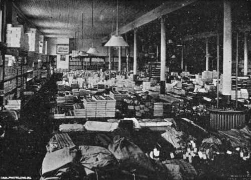 The long, wide room is punctuated by support pillars. Shelves along the walls and tables in rows filling the room are heaped with boxes and stacks of clothing and other goods.