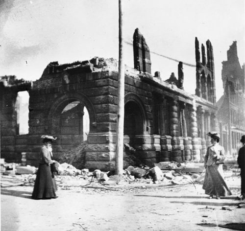Pedestrians walk by the ruins of the Wyld-Darling building. The ground-floor exterior walls and heavy entranceway arches made of cut stone survived the fire.