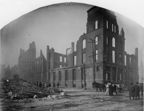 Most of the the ruins are several stories high. Pedestrians and a horse-drawn cart travel the streets, which are mostly clear. To the left, a building has completely collapsed, and cut stone blocks dot the brick rubble.