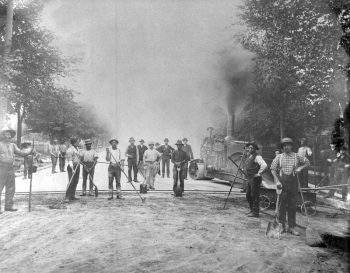 Black men and others use rakes and machinery to pave a road with asphalt.