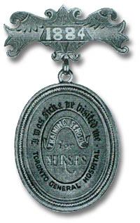 A picutre of an Original blue with black letters Training School for Nurses Pin, 1884