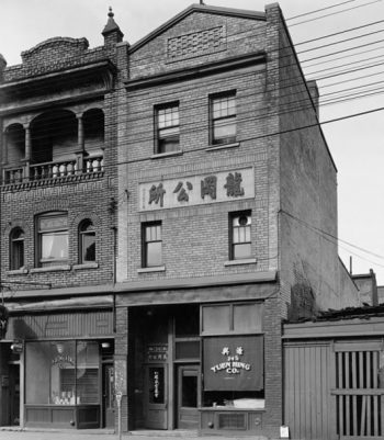 Three-storey brick building with signs in Chinese.