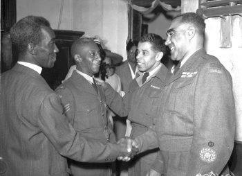 Four Black men, three wearing Canadian Armed Forces uniforms, greet one another