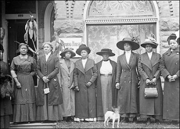 Group of Black women in long coats and broad hats stand in front of an arched window.