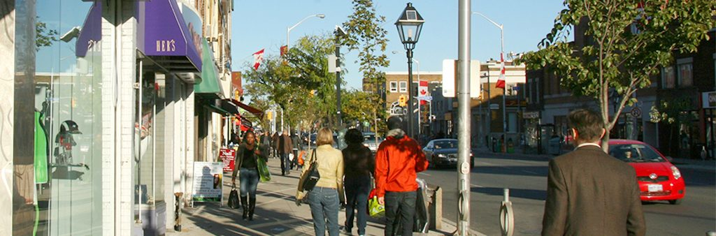 People walking along Bloor street sidewalk next to shop fronts
