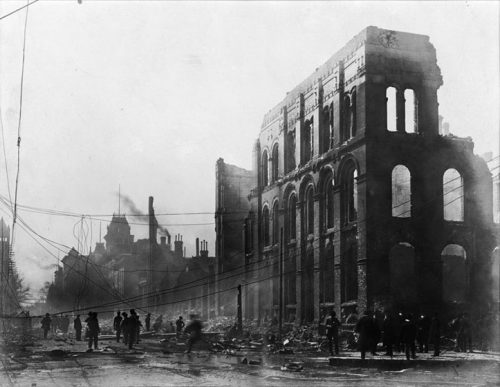 Front Street is lined with ruins, and the street is clogged with rubble and fallen hydro telegraph wires. Many people are viewing the ruins.