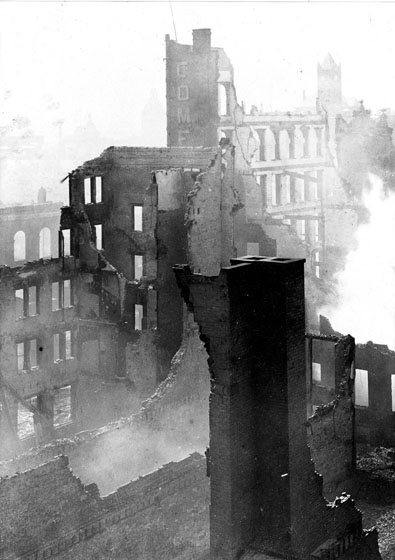 Ruined brick walls, a variety of heights, are viewed from above. Smoke is coming from ground level.
