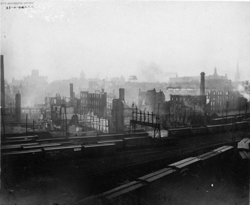 In the foreground are several railway tracks and trains. In the distance are the fire ruins, still smoking.