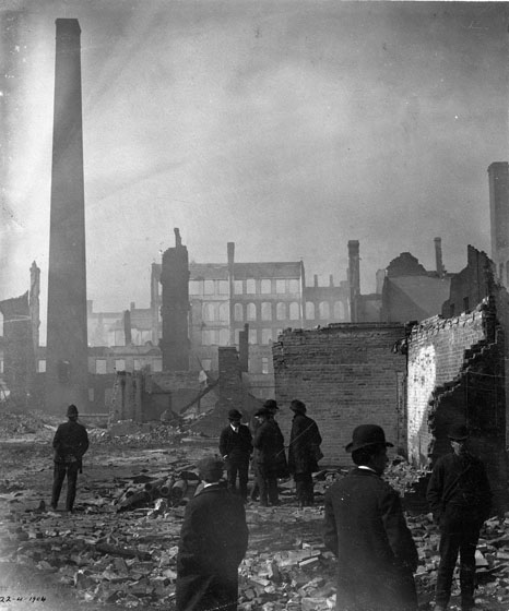 Men in business suits stand around in fire ruins, surrounded by partial brick walls. A tall chimney juts up at the left. In the distance stands a line of building facades with empty windows.