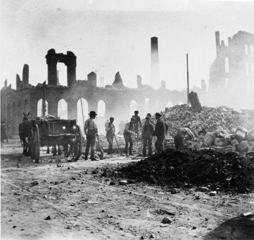 Eight men are preparing to clear a fire ruin site by loading bricks and cut stone into a horse-drawn cart. A few men have shovels. Another seems to be picking up a piece of stone with his hands.