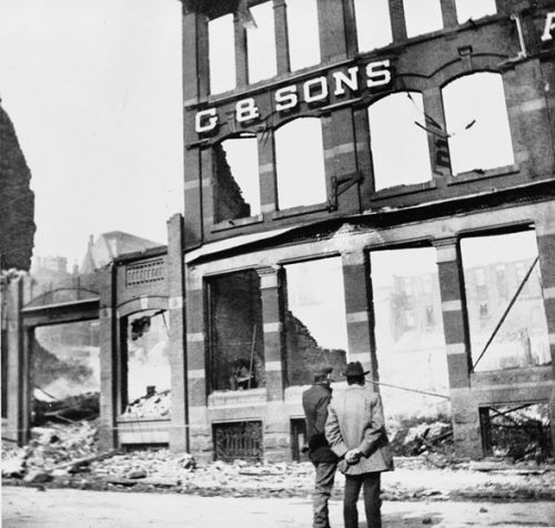Two men stand on the street, looking at the ruins of a building. At least three stories of the brick façade still stand, with empty door- and window-frames. On front of the building are the letters G & SONS.