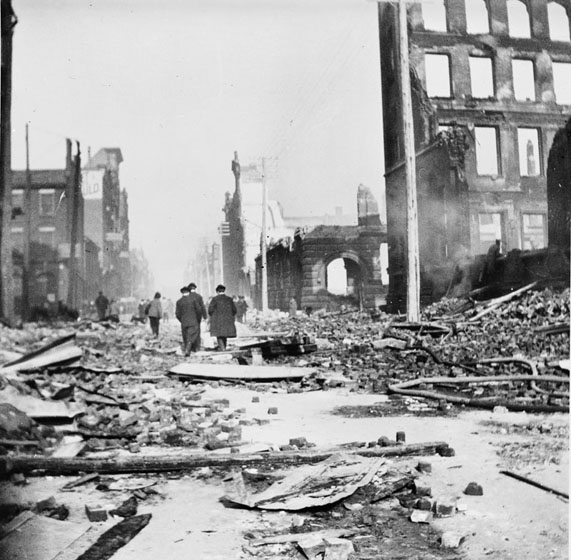 Men walk down the street, away from the camera, surrounded by fire ruins. The street is choked with bricks, timbers, discarded fire hoses, and other litter.