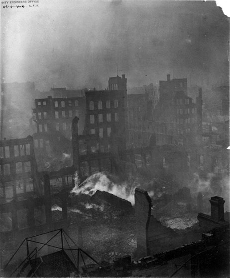 This picture was taken looking down from above, over the fire ruins in the block east of Bay Street. Most of the buildings are destroyed, although some facades, chimneys, and partial walls still stand. The ruins are smoking, and the air is filled with smoke.