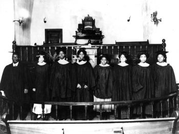 A choir of eight Black men and women in dark robes stands in the chancel of a small church.
