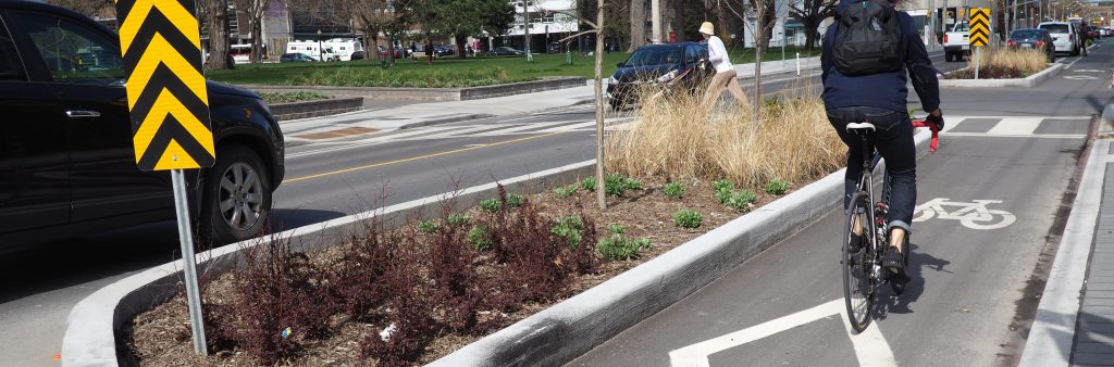Cyclist using the cycle track on Gerrard St E separated by a permanent planter. Background has a pedestrian crossing with a pedestrian pushing a stroller across.