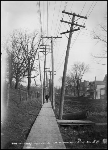 A man walks down a plank sidewalk beside a muddy road. Hydro poles with many wires line both sides of the sidewalk.