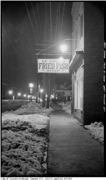 "Looking along a sidewalk, with an overhanging sign saying ""The Superior Fried Fish Shop."""