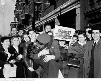 A crowd watches an Air Force pilot and a woman kissing while another woman holds up a newspaper with the headline Germany Surrenders.