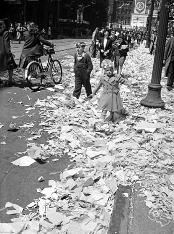 A small girl wades through drifts of tickertape and paper on the street.