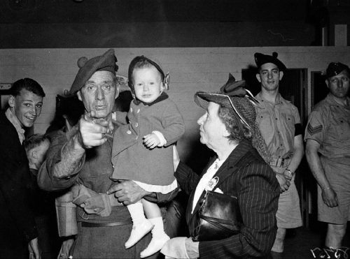 An older man in military uniform holding a little girl points at the camera.