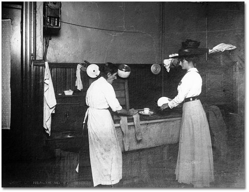 Two women wash dishes in a large rectangular sink.