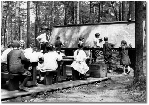 In a clearing in the trees, children sit at desks in front of a blackboard.