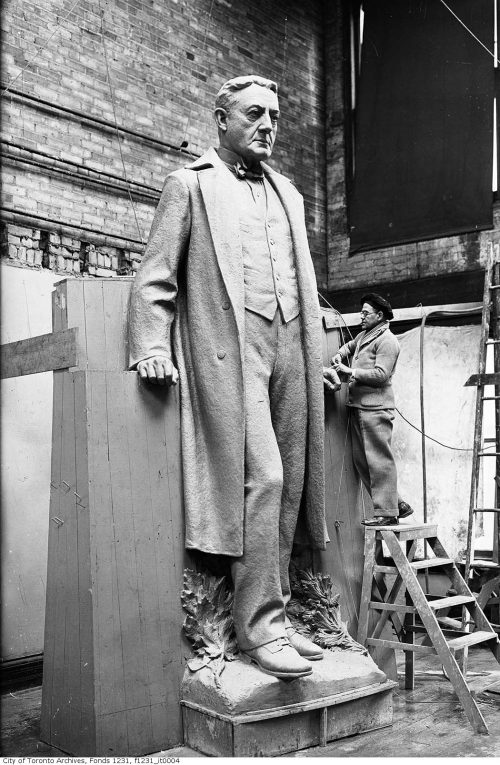 Large stone sculpture of a man in a long coat.