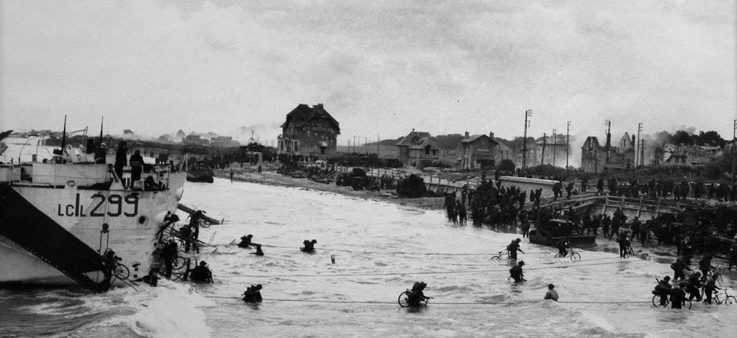 Soldiers carrying bicycles disembark from a troop carrier and wade through the water to a beach. Bombed-out houses line the beach.