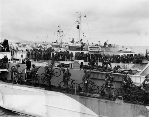 Soldiers holding bicycles line the deck of a ship