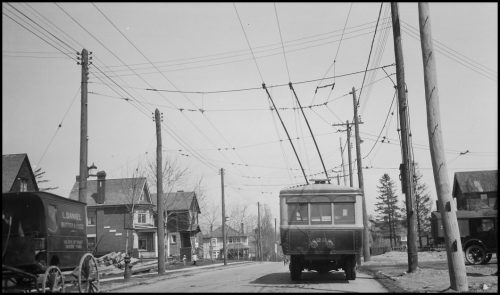 A small square bus with lines leading up to electrical wires above