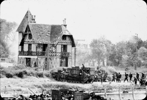 A tank leads a line of soldiers past a Tudor-style house. Its roof is damaged, possibly by the fighting. More houses and trees are in the backrground. More soldiers are in the foreground, just coming into the picutre.