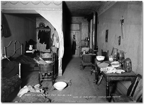 A dark, cluttered room with a wood-burning stove and a table against one wall and beds against the other.