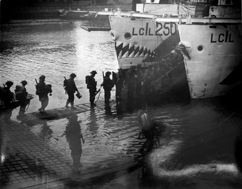 Soldiers, seen in silhouette, walk across narrow wooden gangplanks to troop carriers (ships), one of which has a mouth with sharp teeth painted on its bow.