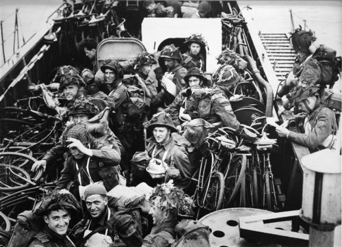 Soldiers and bicycles are packed close together on the narrow deck of a troop carrier. They are wearing helmets and backpacks, and some have equipment hanging across their chests as well.