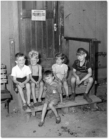 "Kids sitting on a step underneath a ""quarantine"" sign."