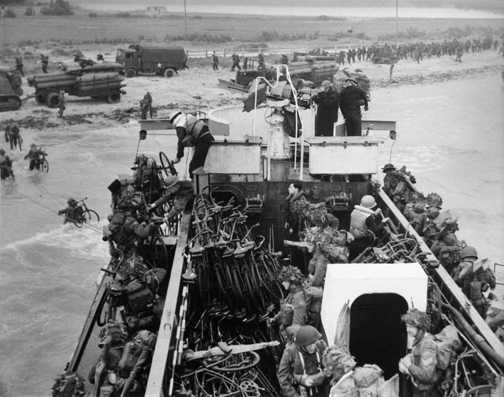 Soldiers carrying bicycles disembark from a troop carrier and wade through the water to a beach, where they are lining up. A truck, a tank, and trailers loaded with ammunition stand on the beach. The land beyond the beach is flat.