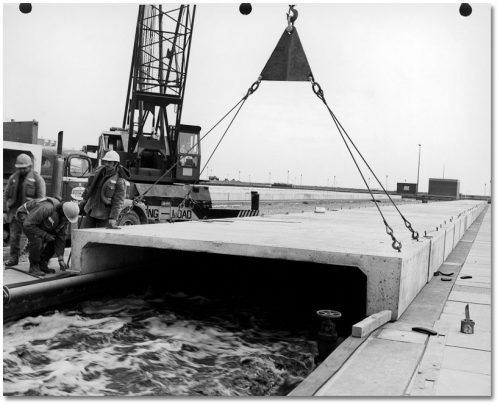A crane lowers a large C-shaped concrete cover over a basin of roiling water.